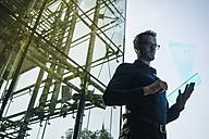 Businessman using futuristic portable device - KNSF01083
