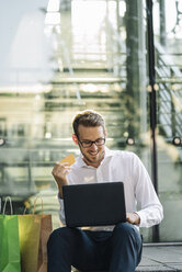 Smiling businessman holding credit card and using laptop next to paper bags - KNSF01107