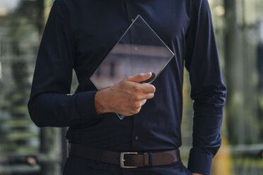 Businessman holding futuristic portable device - KNSF01113