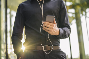 Businessman holding smartphone with connected earphones - KNSF01116