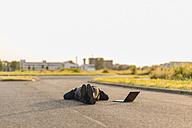 Businessman lying on a road next to laptop - KNSF01125