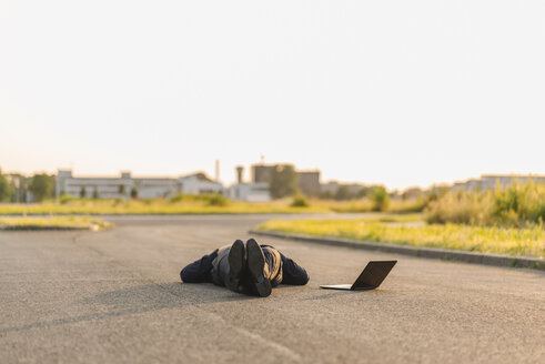 Businessman lying on a road next to laptop - KNSF01125
