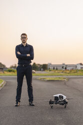 Businessman standing next to drone - KNSF01131