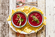 Two bowls of beetroot soup garnished with apple slices, peanuts and flat leaf parsley served with tortilla chips - SARF03207