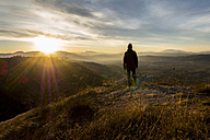Italy, Umbria, Gubbio, Man watching sunrise on Sibillini mountain range - LOMF00518