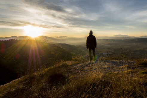 Italy, Umbria, Gubbio, Man watching sunrise on Sibillini mountain range - LOMF00518
