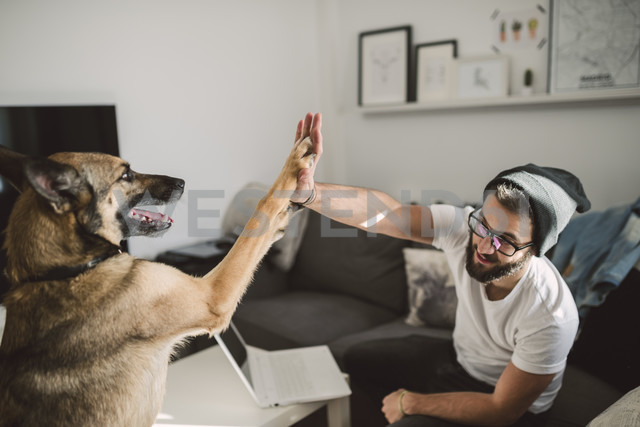 Young man at home giving high five with his dog - RAEF01744 - Ramon Espelt/Westend61