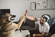 Young man at home giving high five with his dog - RAEF01744