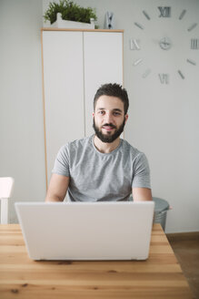 Young man sitting at home, using laptop - RAEF01747