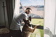 Young man standing at window with his dog, waiting - RAEF01750