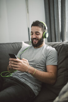 Young man sitting on sofa, listening music from his smart phone - RAEF01753