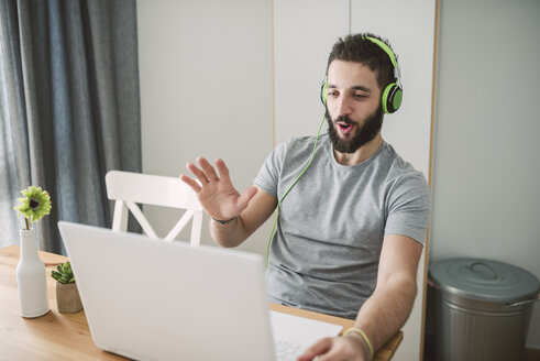 Young man wearing headphones, using laptop at video conference - RAEF01756