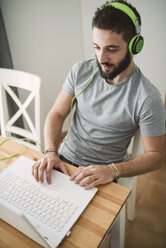 Young man wearing headphones, using laptop - RAEF01759