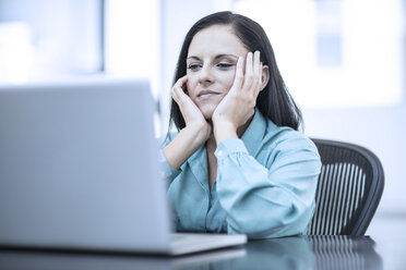 Woman with her head in her hands sitting in a office behind computer - ZEF12977