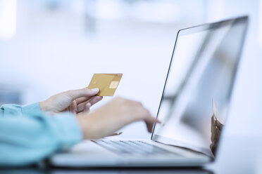 Woman holding credit card and typing on computer making an onliine payment - ZEF12980