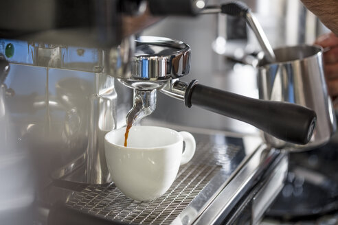 Coffee from espresso machine pouring into cup - ZEF12995