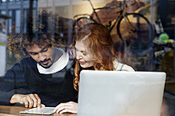 Young couple with laptop and menu behind windowpane - FMKF03493