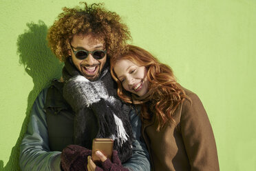 Happy young couple looking at cell phone at green wall - FMKF03508