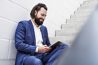 Smiling businessman using tablet on stairs - FMKF03523