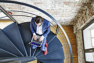 Businessman using laptop on spiral staircase - FMKF03541