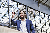 Smiling businessman taking a selfie - FMKF03553