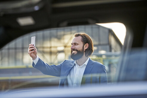 Smiling businessman taking a selfie outside car - FMKF03559
