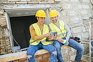 Two construction workers looking at a cell phone at break time - KIJF01247