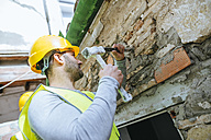 Construction worker working with hammer and chisel - KIJF01250