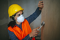 Woman on construction site leveling wall - KIJF01262