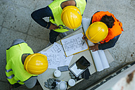 Woman and two men in workwear discussing construction plan - KIJF01268