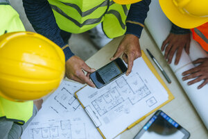 Woman and two men in workwear taking cell phone picture of a construction plan - KIJF01271