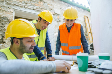 Smiling woman and two construction workers on construction site - KIJF01274