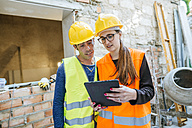 Woman with tablet talking to construction worker on construction site - KIJF01277