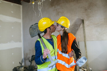 Couple in workwear kissing on a construction site - KIJF01286