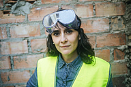 Portrait of confident woman wearing safety glasses on construction site - KIJF01289