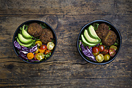 Lunch bowls of leaf salad, red cabbage, avocado, tomatoes and quinoa fritters - LVF05900