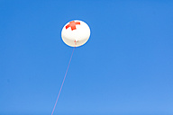 Germany, Munich Red Cross balloon in front of blue sky at Oktoberfest - MMAF00053