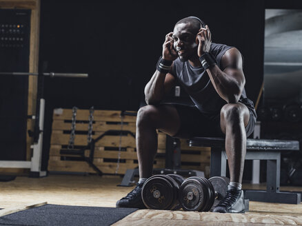 Athlete sitting in gym, wearing headphones, concentrating - MADF01364
