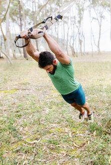 Man doing suspension traning outdoors - MGOF03004