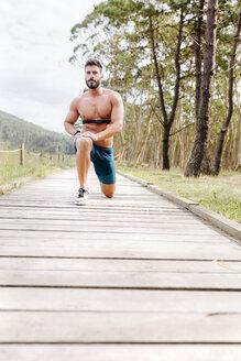 Barechested man exercising on boardwalk - MGOF03010