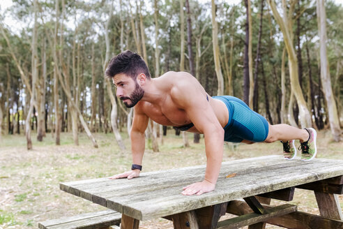 Barechested man doing push-ups on wooden table outdoors - MGOF03013