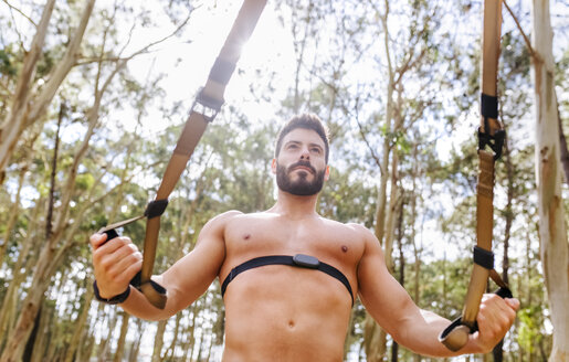 Barechested man doing suspension traning outdoors - MGOF03016