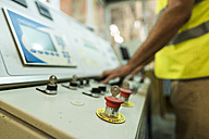 Worker in concrete factory pressing button on control panel - JASF01551