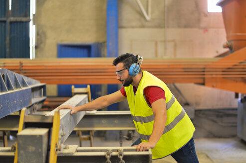 Worker in concrete factory cutting steel, wearing ear defenders - JASF01560