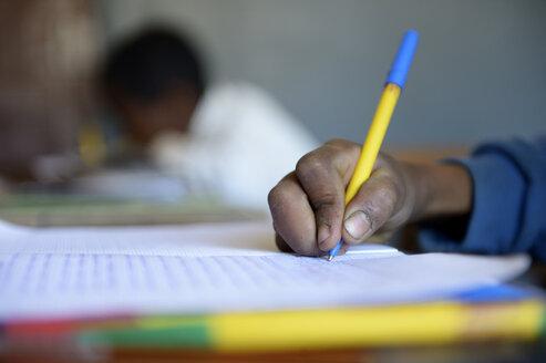 Madagascar, Fianarantsoa, Schoolboy writing in notebook - FLKF00742