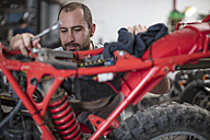 Mechanic working on motorcycle in workshop - ZEF13023