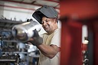 Mechanic in workshop holding motorcycle exhaust - ZEF13032