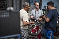Mechanics standing together in motorcycle workshop - ZEF13035