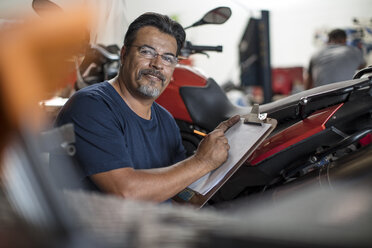 Portrait of smiling mechanic with clipboard in motorcycle workshop - ZEF13050