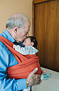 Great-grandfather carrying baby in a baby sling - GEMF01513